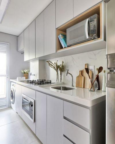 Cozinha cinza planejada com bancada branca e acessórios.