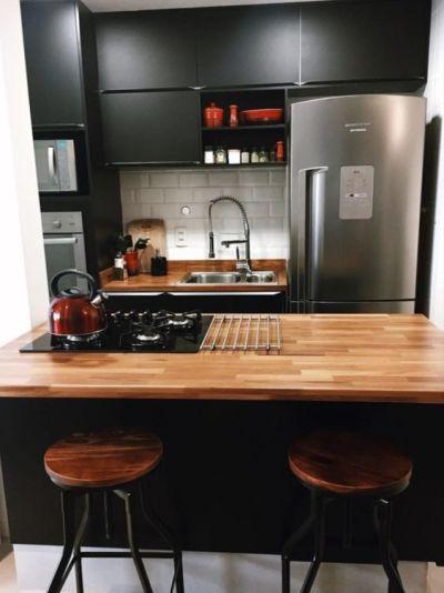 Cozinha planejada preta com bancada de madeira