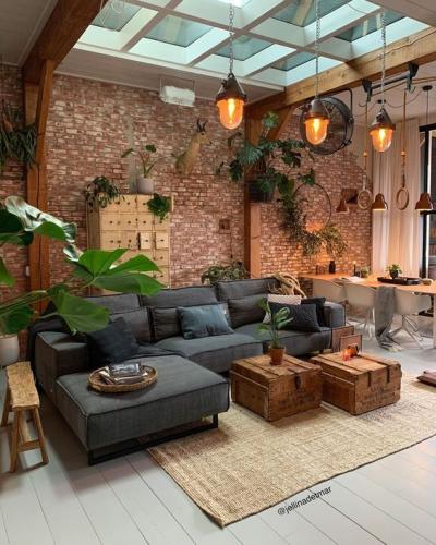 Decoração rústica e moderna com sofá preto e parede de tijolinho e objetos rústicos