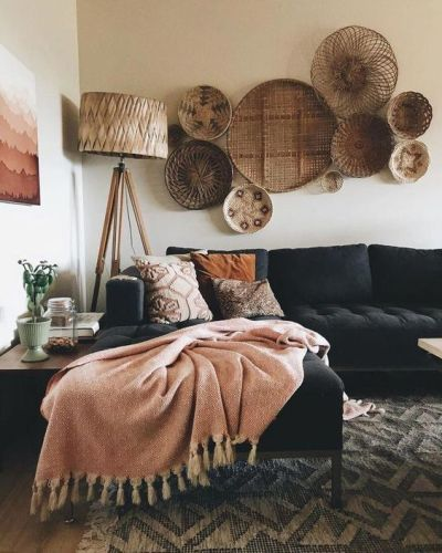 Sofá preto na sala com manta, almofadas e cestos na parede