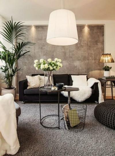 Sala grande com sofá preto, cimento queimado e palmeira grande lateral