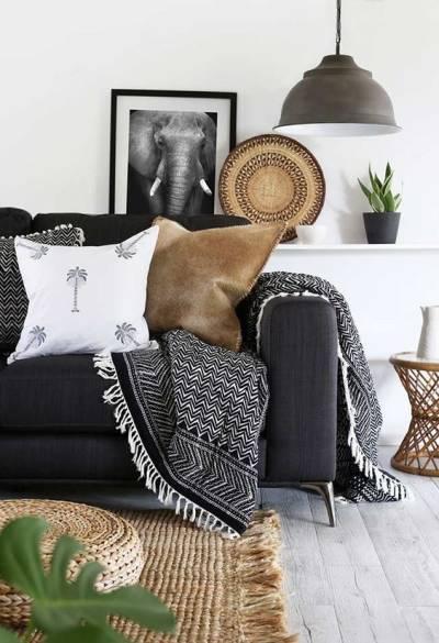 Sofá preto com almofadas e manta