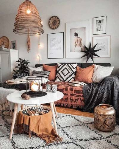 Sala com sofá preto e almofadas estilo boho chic