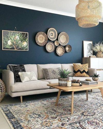 Sala com sofá cinza decorada com cestos na parede azul