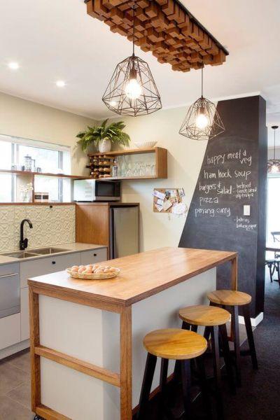 Parede lousa na cozinha com ilha e banquetas