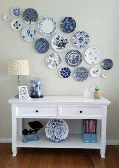 Parede decorada com pratos com móvel branco