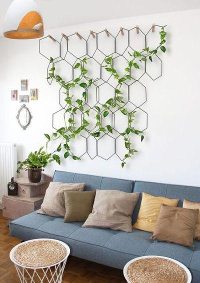 Sala com sofá cinza e parede com planta jibóia