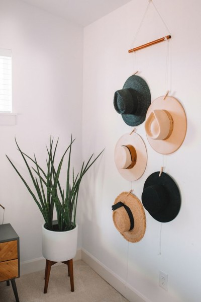 Canto de sala com planta e chapéu pendurado