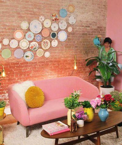 Sala com Parede de tijolinho com pratos e sofá rosa