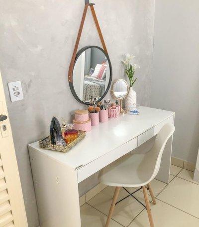 Penteadeira branca com parede de cimento queimado e cadeira eames