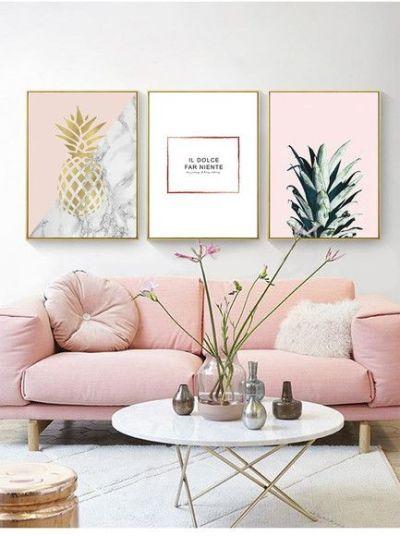 Sofa rosa claro com quadros na parede e mesa de centro