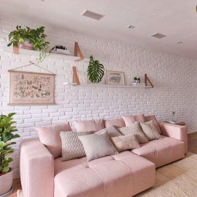 Sofá retrátil rosa claro e parede de tijolinho branco