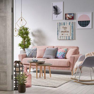 Sala com sofá rosa e quadros na parede