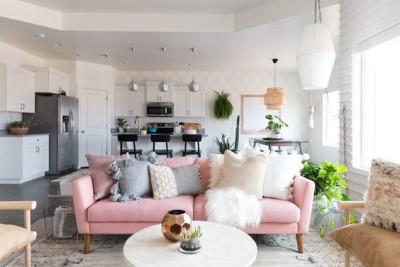 Sala grande com sofá rosa com almofadas