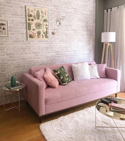 Sofá rosa bebe com almofadas e parede com papel de parede de tijolinho cinza