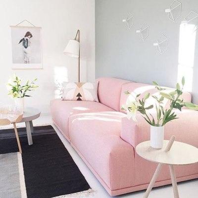Sofa rosa claro em sala com parede cinza