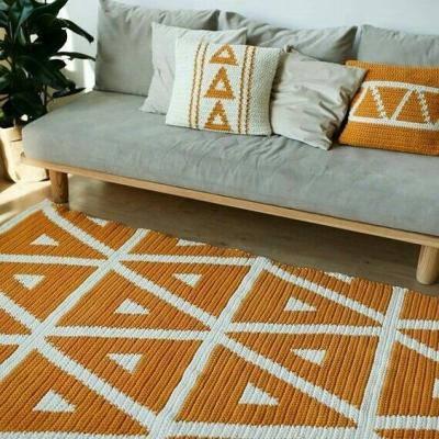 Tapete colorido geométrico e almofadas no sofá cinza