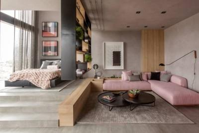Sala com sofá rosa de canto e parede e piso de cimento queimado