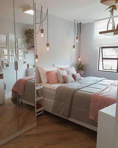 Tons pasteis no quarto - armário espelhado, cama com almofadas e luminária pendente.