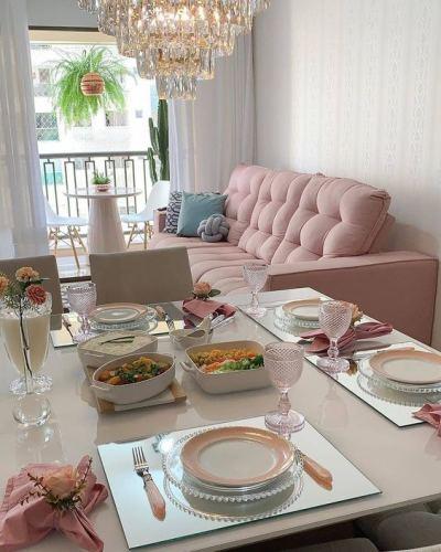 Sofa retrátil rosa em sala pequena com mesa de jantar