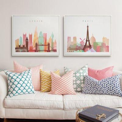 Tom pastel com sofá com almofadas e dois quadros na parede.