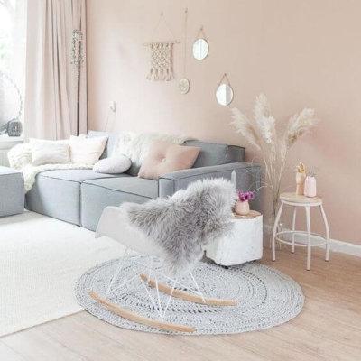 Tom pastel na sala com parede pintada de rosa e sofá cinza