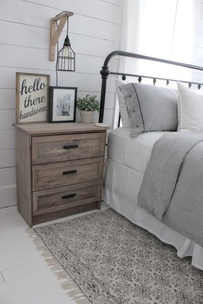 Decoração de quarto de casal rústico com cabeceira de ferro e mesa lateral de madeira