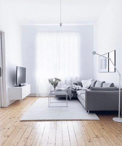Decoração minimalista na sala com sofá cinza e chão de madeira