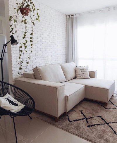 Decoração minimalista com tons claros  na sala com parede de tijolinho