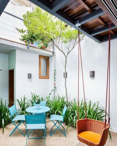 Quintal pequeno decorado com mesa, cadeiras, plantas e balanço