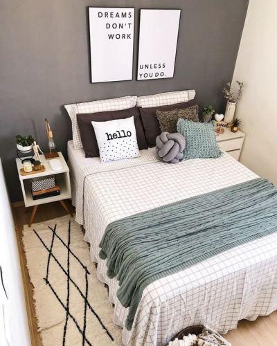 Quarto decorado com parede pintada de cinza, almofadas e quadros