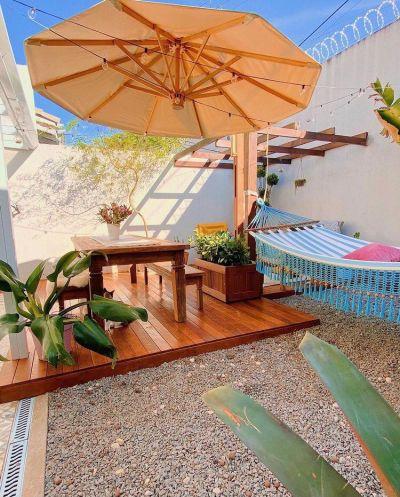 Decoração de quintal de casa com deck de madeira e rede