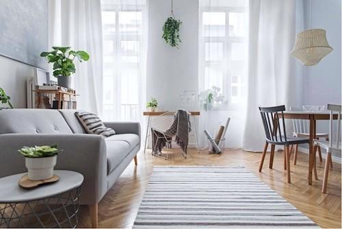 Sala pequena estilo escandinavo minimalista com sofá cinza e tapete