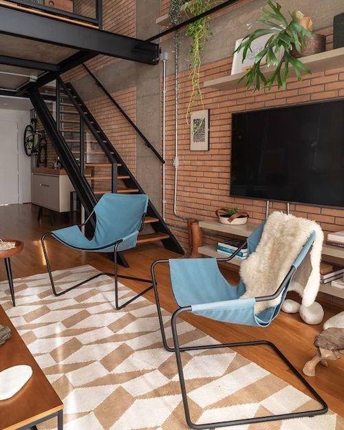 Decoração industrial na sala com parede de tijolinho, escada e cadeiras