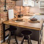 Cozinha americana com decoração industrial e parede de tijolinho aparente