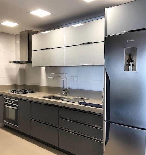 Cozinha preta e branca planejada com cooktop e forno embutido