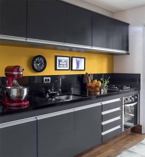 Cozinha preta e amarela planejada com forno embutido e cooktop