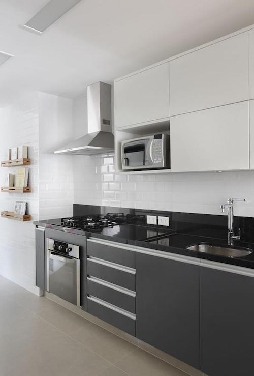 Cozinha preta e branca planejada com cooktop e fogão embutido