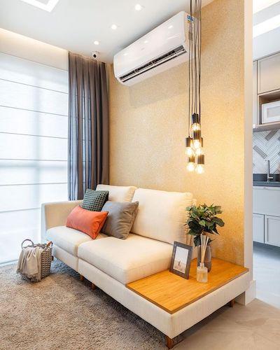 Decoração de Sala pequena com tapete e sofá bege pequeno e luminária pendente