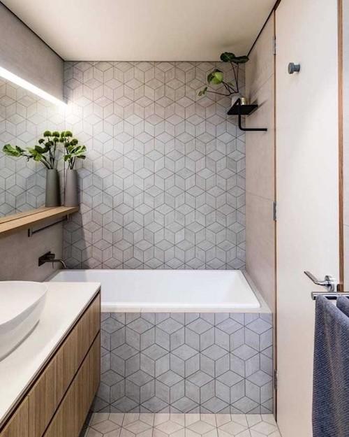 Banheiro com revestimento geométrico cinza e banheira moderna
