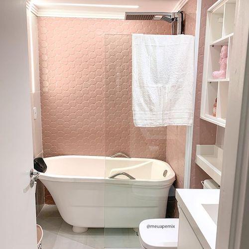 Banheiro com banheira simples e revestimento rosa na parede