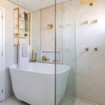 Banheiro com banheira de imersão pequena branca e prateleira