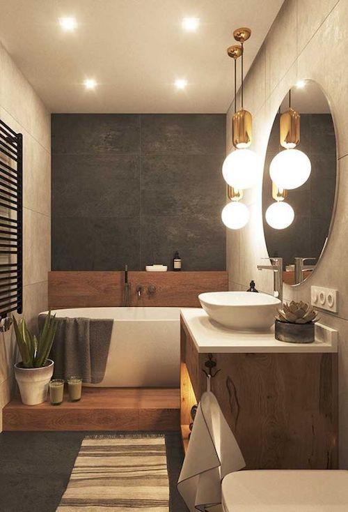 Banheiro com espelho redondo e banheira pequena